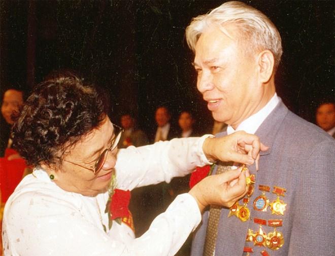Phó Chủ tịch Nước Nguyễn Thị Bình gắn huy hiệu Anh hùng Lao động cho ông Đặng Văn Thân